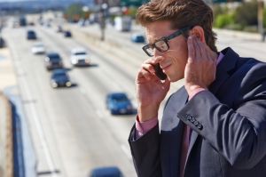 Businessman Speaking On Mobile Phone By Noisy Freeway