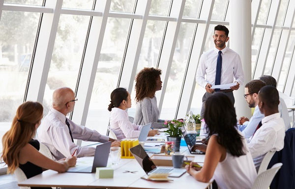 Hispanic Businessman Leading Meeting At Boardroom Table
